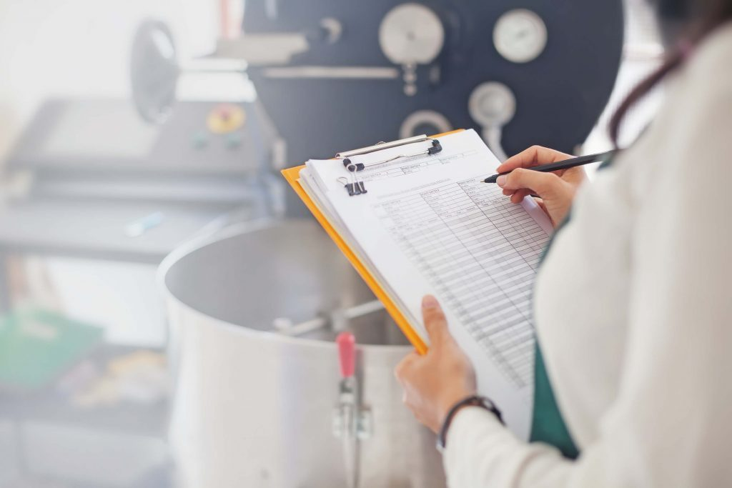 A woman taking notes on a clipboard in a food production facility.
