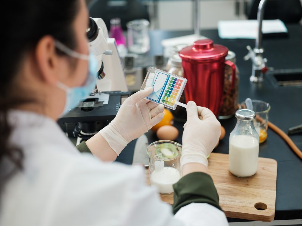 A woman in a lab testing milk with color strips